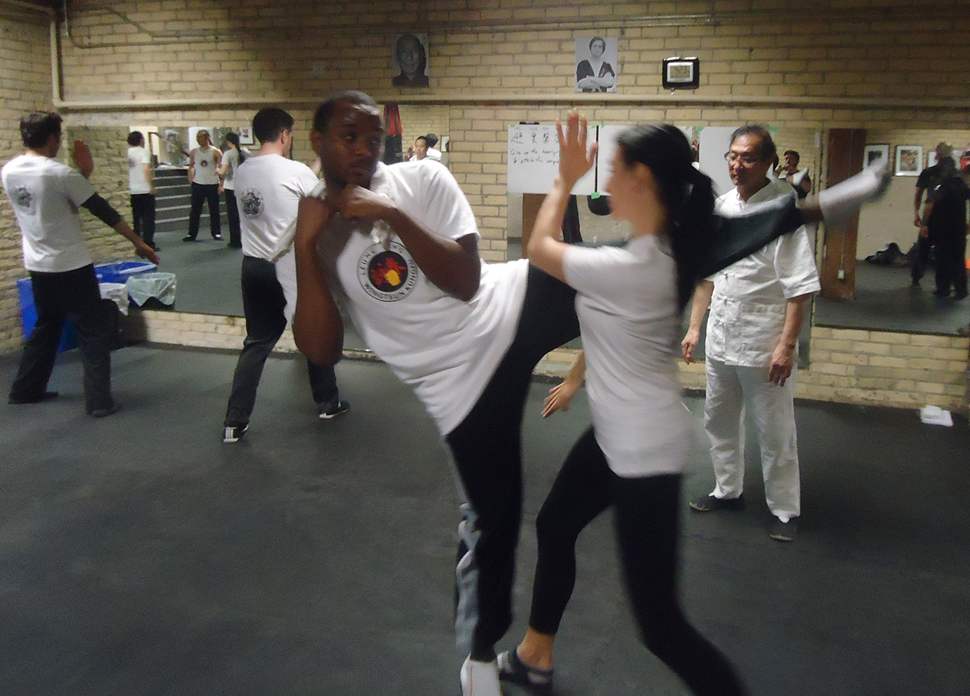 Photo: Great Grandmaster Leung Ting watches students practice defending high kicks in Toronto, Canada
